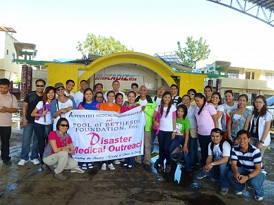 After a relief operation, a disaster response team from Bacolod Adventist Medical Center pose in front of the stage of what used to be a covered court/gymnasium in Cadiz City, one of the places hit by Typhoon Haiyan with its fast winds tearing apart houses and buildings on November 8 (Photo provided by Jo Anne Amparo)