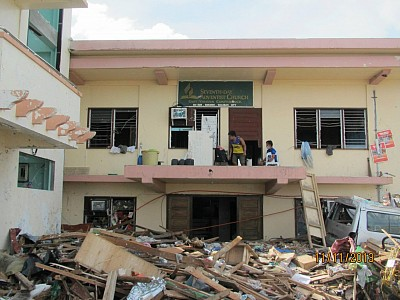 The Adventist church headquarters in east Visayas located in Tacloban surrounded by huge piles of debris in the aftermath of typhoon Haiyan that hit the city on November 8. Church leaders & members now try to clear the area surrounding the office to provide a place for relief operation. [photo by Luna Casio]