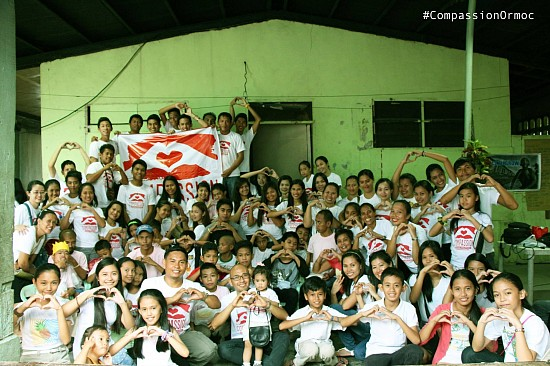 Adventist Youth in Ormoc City hold up their hand-heart signs to the camera surrounded with children from the local social welfare center after a children's program and food distribution. (photo grabbed from OYIM-CPUC Facebook page)